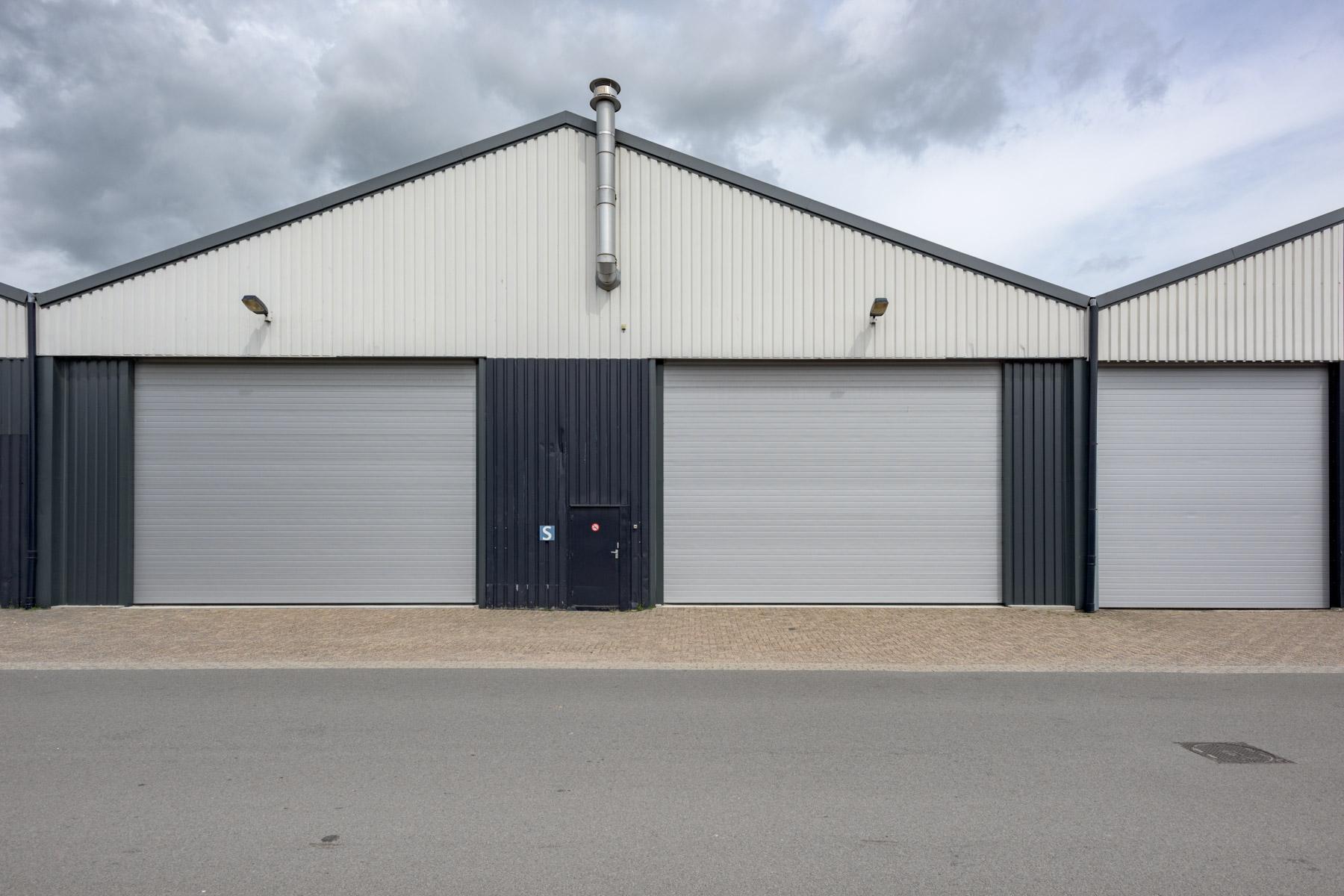 Bedrijfsdeuren: Sectionaaldeur grijs in gevel loods | Louwers Deurtechnieken