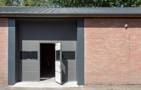 Bedrijfsdeuren: Overheaddeur met glaspanelen en loopdeur | Louwers Deurtechnieken