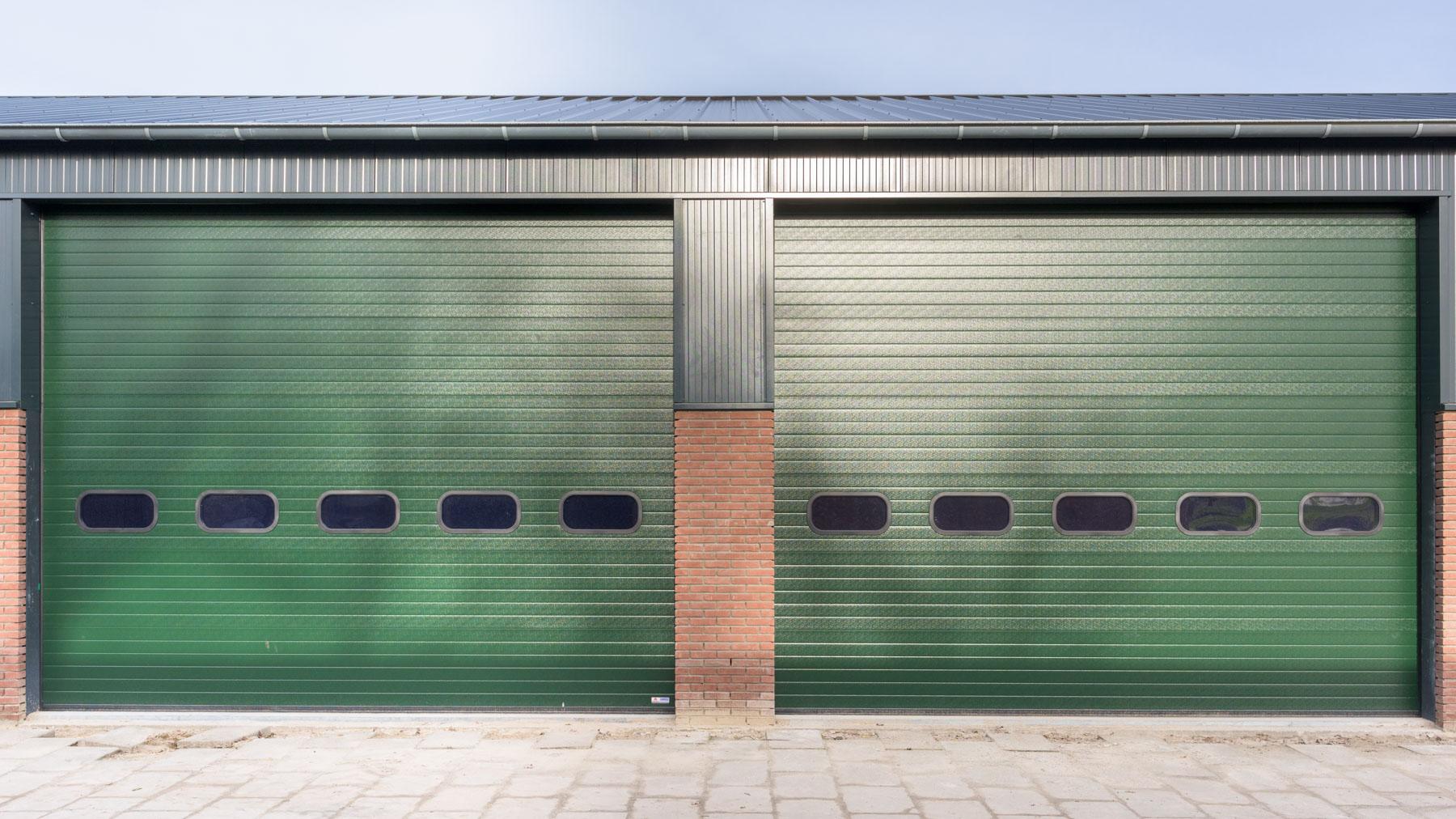 Bedrijfsdeuren: Groene overheaddeuren met ovale vensterramen | Louwers Deurtechnieken